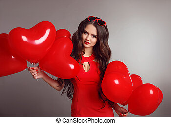 Attractive love portrait brunette woman in red with heart balloons isolated on gray studio background. Valentine day. Birthday party.