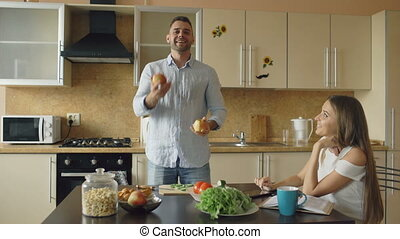 Attractive loving couple having fun in the kitchen. Handsome man juggle with apples to impress his girlfriend
