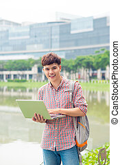 Attractive male asian student is using laptop in campus