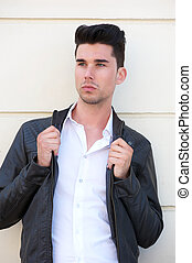 Attractive male fashion model holding black leather jacket