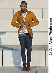Attractive male fashion model holding jacket outdoors
