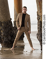 Attractive male fashion model on beach