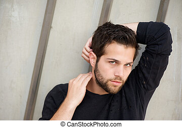 Attractive male fashion model posing with hands behind head