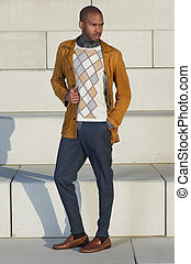 Attractive male fashion model standing outdoors