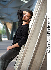 Attractive male fashion model with beard posing outdoors