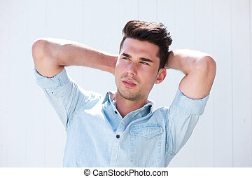 Attractive male fashion model with hands in hair