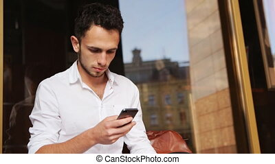 Attractive male in his 20s texting on smartphone outdoors.