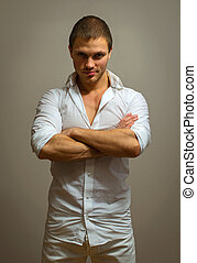 Attractive male model posing on grey background.
