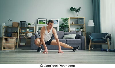 Attractive male sportsman stretching legs during individual...