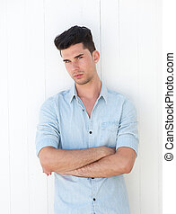 Attractive male with arms crossed on white background