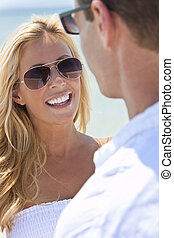 Attractive Man and Woman Couple In Sunglasses At Beach