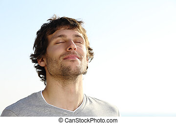 Attractive man breathing outdoor with the sky in the ...