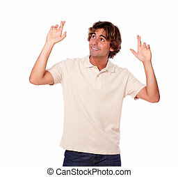 Attractive man crossing fingers while looking up