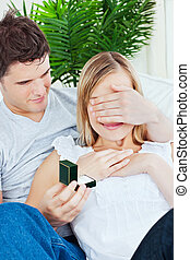 attractive man doing a surprise to his girlfriend with a wedding ring in the living-room