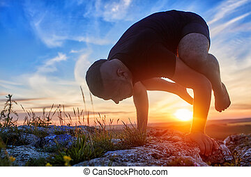 Attractive man doing yoga on the rock in the morning against sunrise.