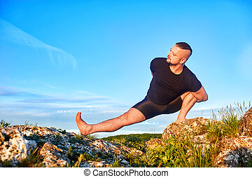 Attractive man doing yoga on the stone against bright blue sky with clouds.