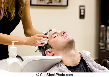 Attractive man having a shampoo in a hairdressing salon
