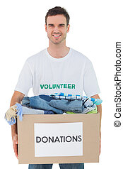 Attractive man holding donation box with clothes on white...