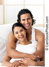 Attractive man hugging his wife lying on the bed