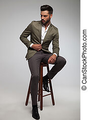 attractive man in green suit sits on wood stool - attractive...