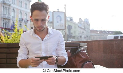 Attractive man in his 20s sitting on a bench using...