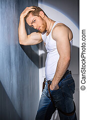 attractive man in shirt standing near the wall in the...