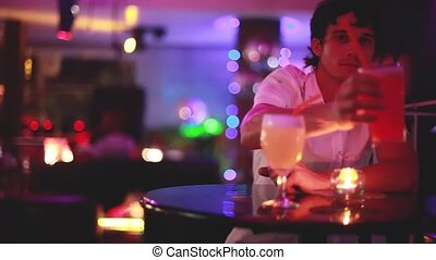 Attractive man is drinking cocktail in a night club on...