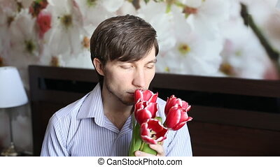 Attractive man is smelling the flowers and stay into a...