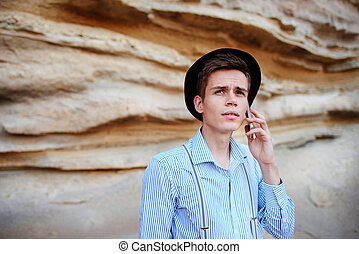 Attractive man is standing in the middle of a sand quarry and ma