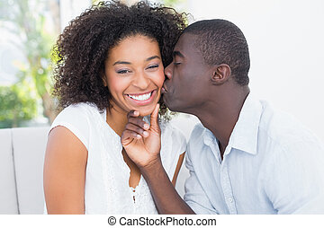 Attractive man kissing his girlfriend on the cheek at home...