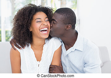 Attractive man kissing his girlfriend on the cheek at home in the living room