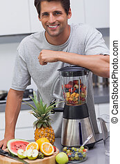 Attractive man leaning on his blender with several fruits...