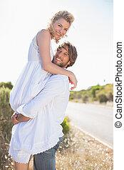 Attractive man lifting up his girlfriend smiling at camera