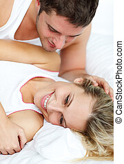 Attractive man looking at his girlfrined in bed