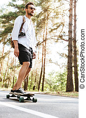 Attractive man on skateboard outdoors