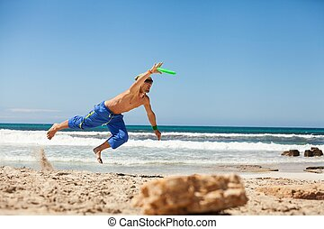 attractive man playing frisby on beach in summer sport...
