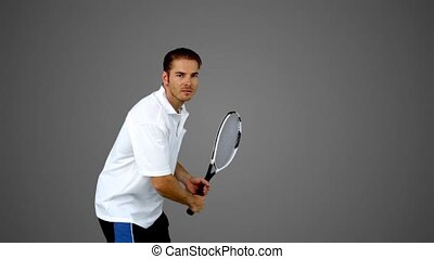 Attractive man playing tennis on gr