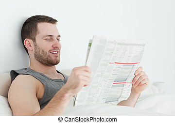 Attractive man reading a newspaper