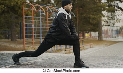 Attractive man runner doing stretching exercise preparing for morning workout and jogging in winter park