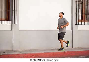 Attractive man running outdoors