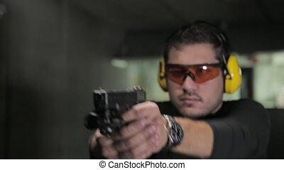 Attractive man shooting bullets - pistol shooting indoor