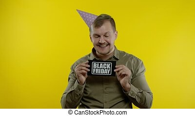 Attractive man in festive cap smiling and showing Black Friday text inscription. Holiday discounts, low prices for online shopping. Black Friday concept. Yellow background. 6k downscale, slow motion