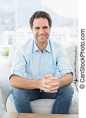Attractive man sitting on the couch smiling at camera