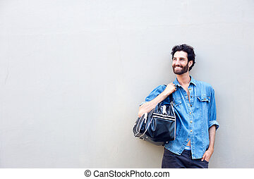Attractive man smiling and holding travel bag over shoulder