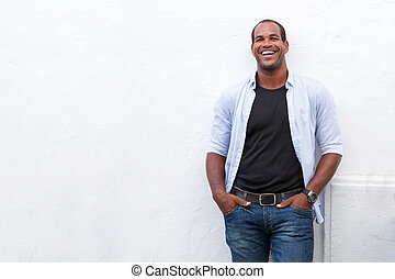 Attractive man standing and laughing on white background
