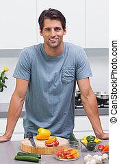 Attractive man standing in his kitchen