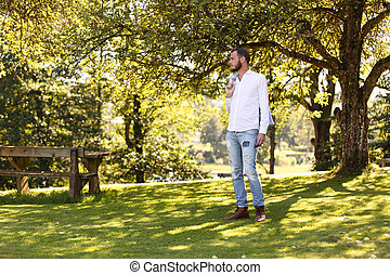 A man standing on green grass with trees behind him, wearing a white shirt and jeans, and holding a blazer on his shoulder. A sunny summer day.