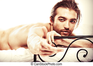 attractive man - Handsome nude man lying in a bed. Isolated...