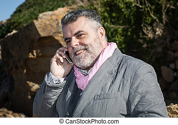 Attractive man talking on the phone to the sea