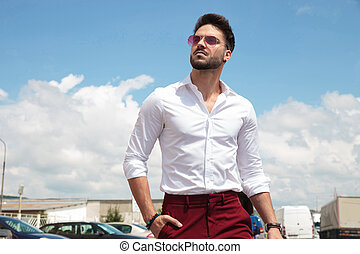 attractive man wearing sunglasses walking in parking lot